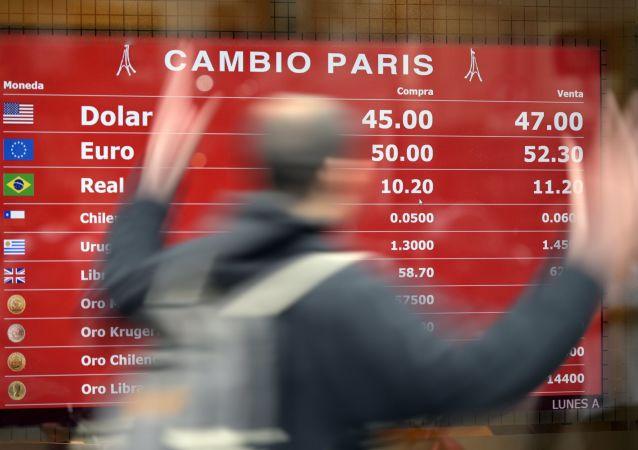Una pizarra con cotizaciones de monedas extranjeras en Argentina
