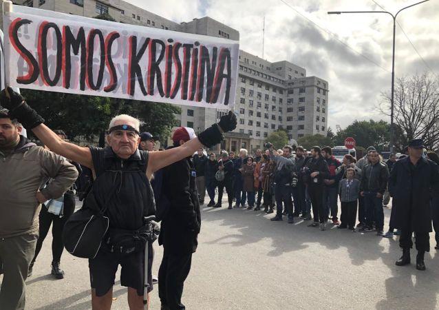 Un hombre sostiene una pancarta en apoyo a Cristina Fernández fuera de tribunales