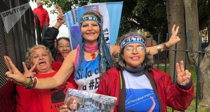 Simpatizantes de Cristina Fernández saludan a la cámara fuera de la sede judicial de Comodoro Py