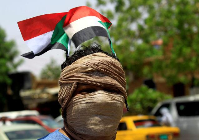 Un manifestantes con la bandera de Sudán