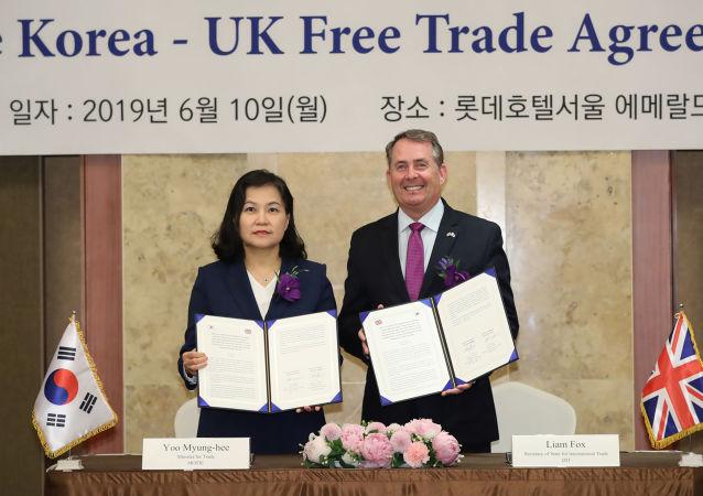 La ministra surcoreana de Comercio, Yoo Myung-hee, y el secretario de Estado británico para Comercio Internacional, Liam Fox