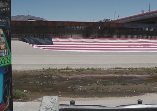 Un estadounidense despliega una bandera de ''Estados Unidos de Migrantes''
