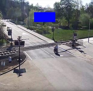 Un tren casi se lleva a un motorista por delante