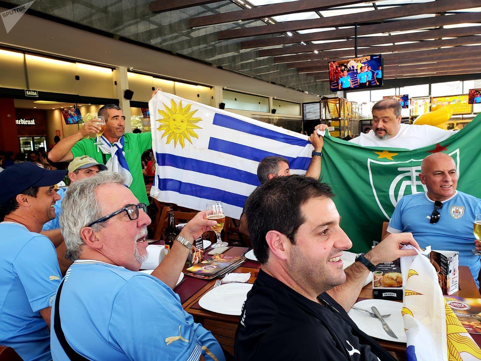 Hinchas de Uruguay miran el partido contra Ecuador en un bar