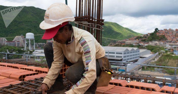 Una mujer en la construcción de los edificios que conformarán el complejo urbanístico llamado 'Jorge Rodríguez Padre', que cuenta con el apoyo financiero del Gobierno y es construido por los que serán sus propietarios 80% mujeres