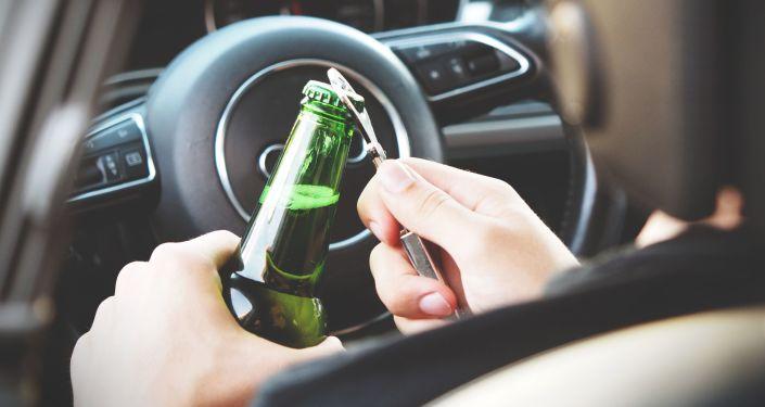 Persona abriendo una botella de alcohol en un auto