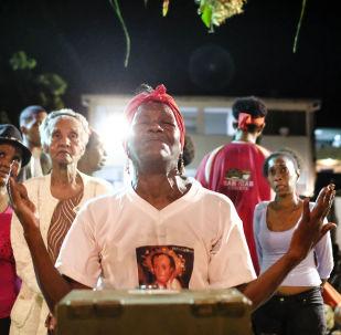 Una mujer reza frente a la estatuilla de San Juan durante la celebración del Día de San Juan Bautista en Curiepe.