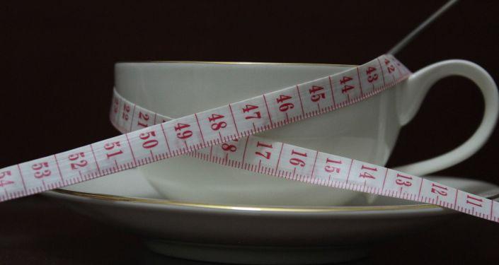 Una cinta métrica y una taza