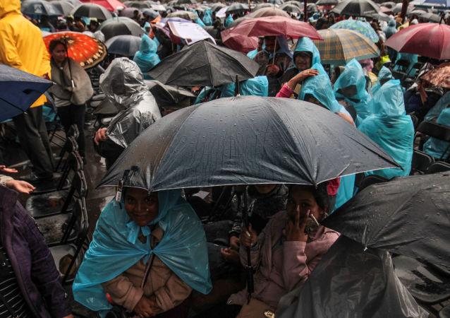 Asistentes se cubren de la lluvia durante el evento para la presentación del informe de actividades del presidente Andrés Manuel López Obrador en el Zócalo Capitalino