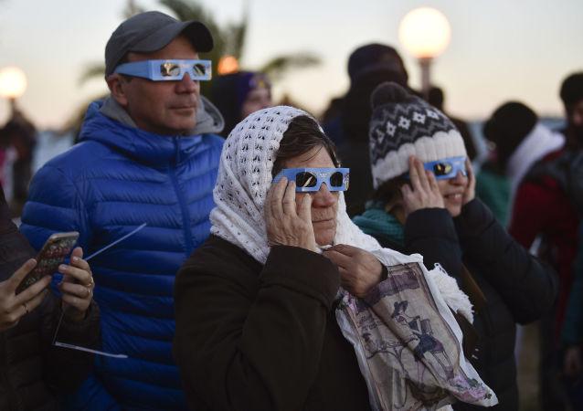 Argentinos miran el eclipse de Sol en la localidad de Chascomús, en la provincia de Buenos Aires