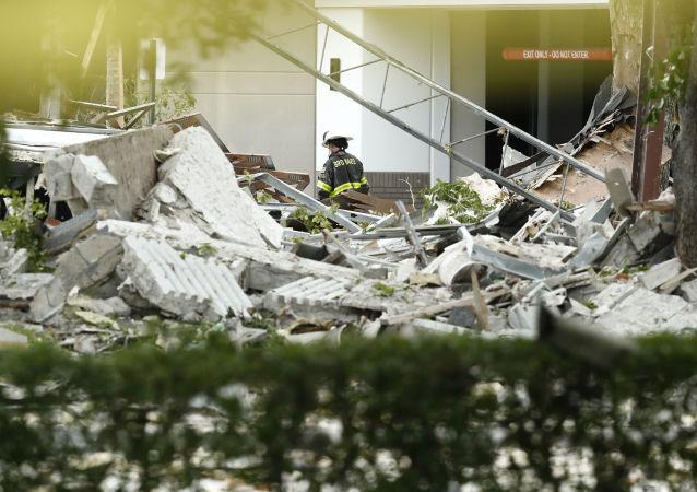 Un funcionario camina cerca de los escombros después de una explosión el 6 de julio de 2019 en Plantation, Florida.