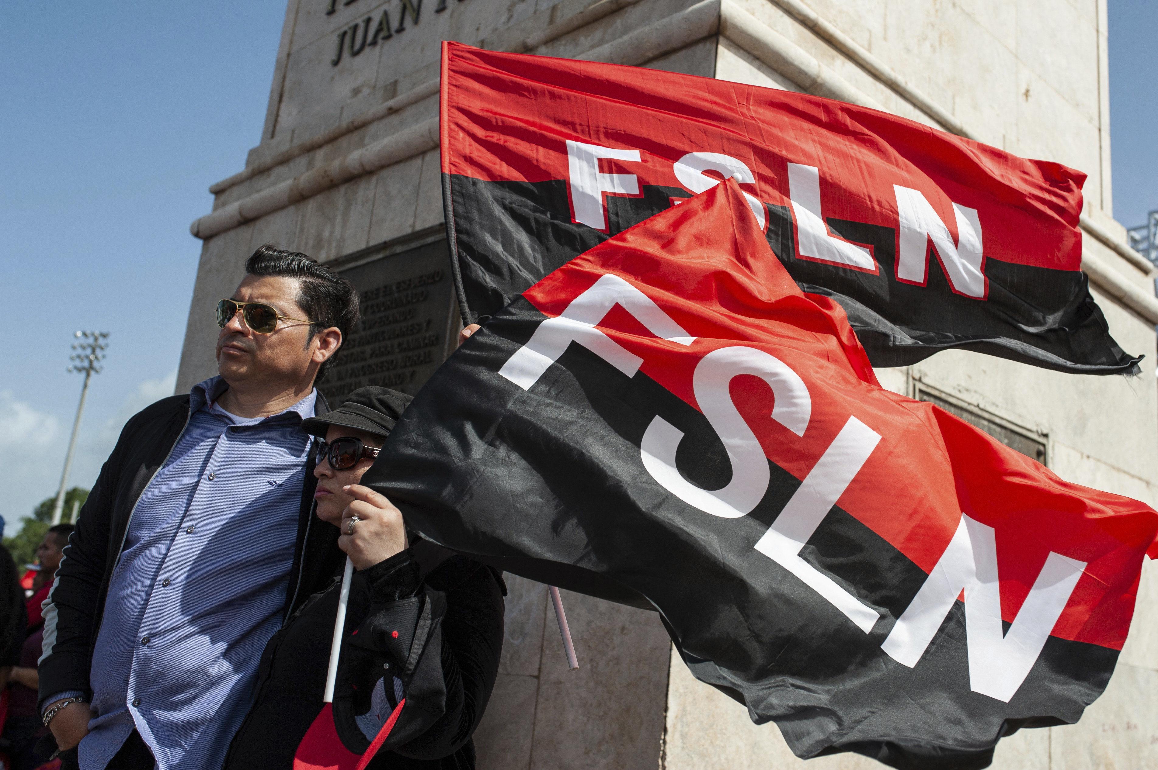 Sandinista porta las banderas del FSLN en el aniversario de la Revolución nicaraguense