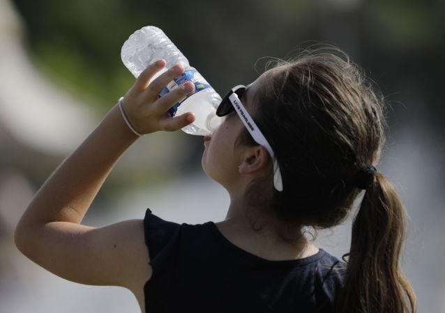 Una joven bebe agua durante la ola de calor que azotó Europa el verano de 2019 (archivo)