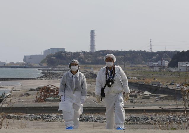 Personas en trajes de protección cerca de la planta nuclear Fukushima 2