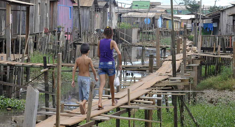 Altamira, Pará, Brasil - En medio de un saneamiento deficiente, los residentes se balancean en calles de madera para llegar a sus hogares.