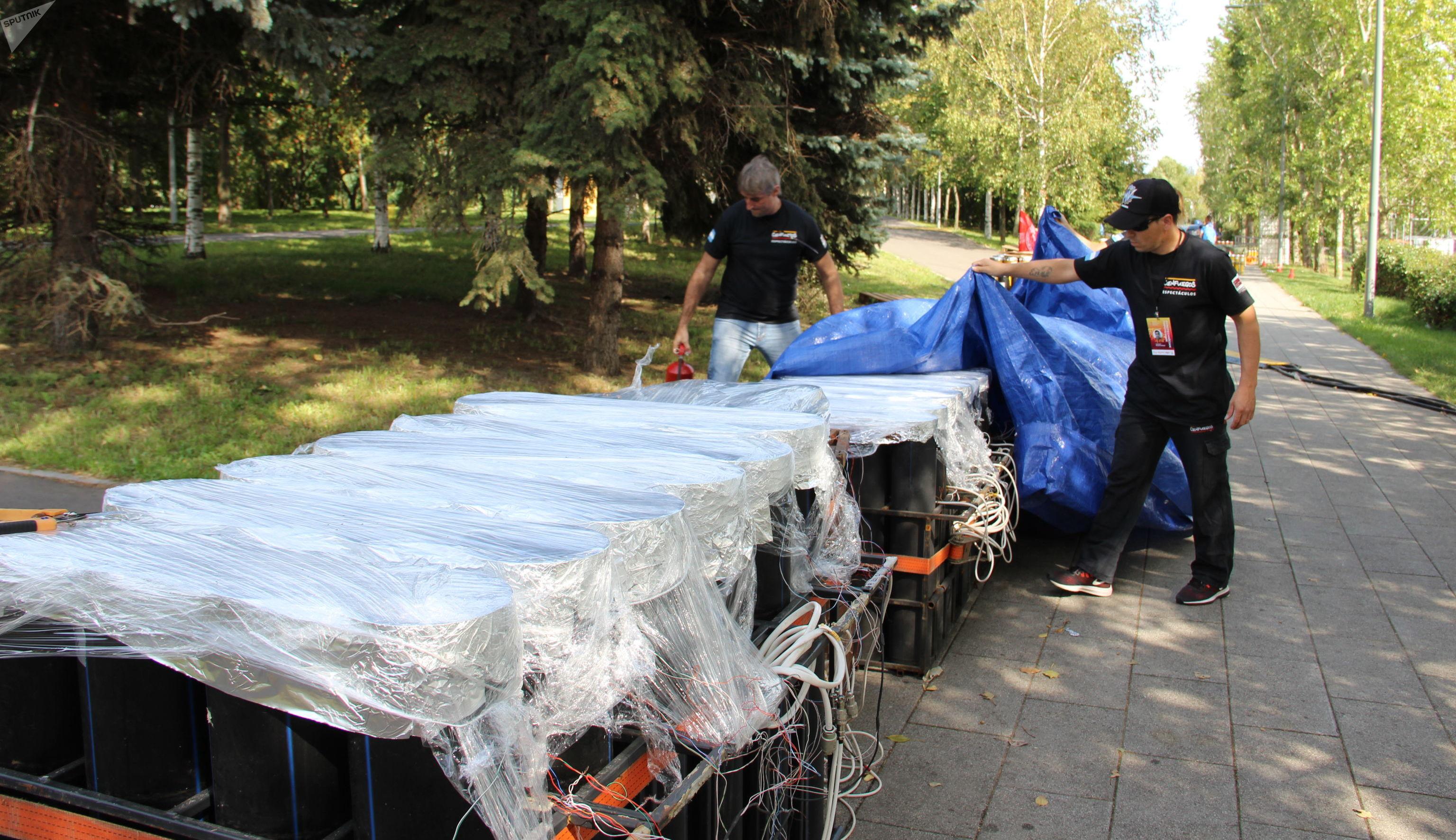 Los miembros del equipo argentino cubren sus fuegos artificiales para protegerlos de posibles lluvias en los días anteriores al festival