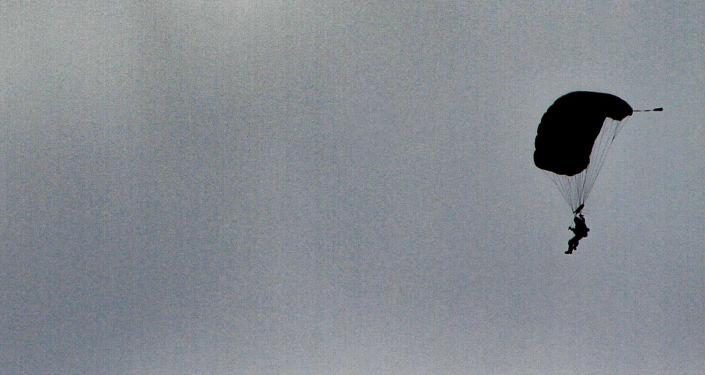 Miembro de las fuerzas armadas desciende de un paracaídas como parte de la exhibición del desfile militar