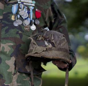 El veterano de la Guerra de las Malvinas muestra su casco dañado en el campo de batalla
