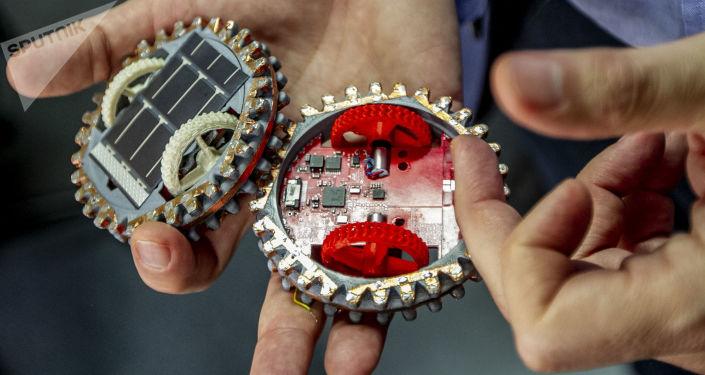 Gustavo Medina, investigador del Instituto de Ciencias Nucleares muestra dos pequeños robots que viajarán a la luna en 2021