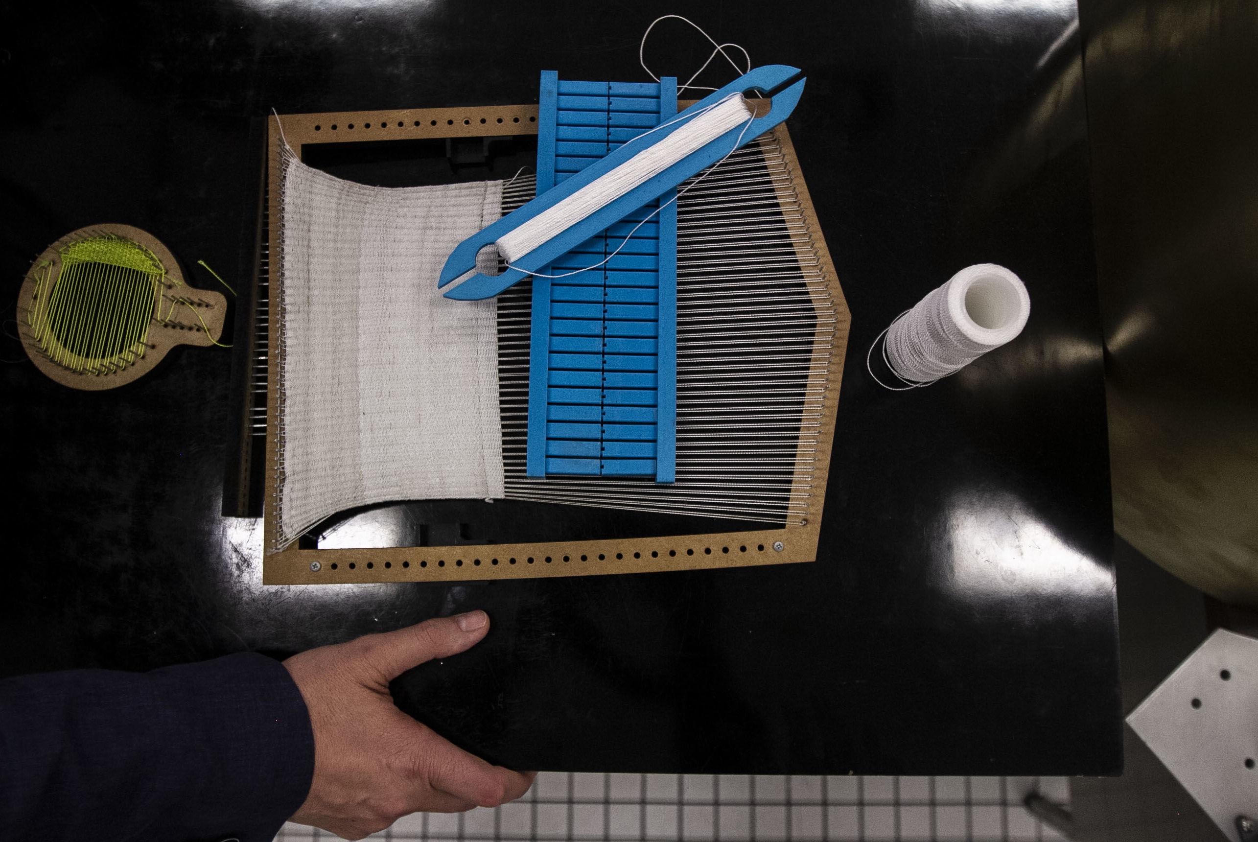 Gustavo Medina, investigador del Instituto de Ciencias Nucleares muestra un telar que se utiliza para construir parte del sistema que hará viajar nueve pequeños robots mexicanos a la Luna