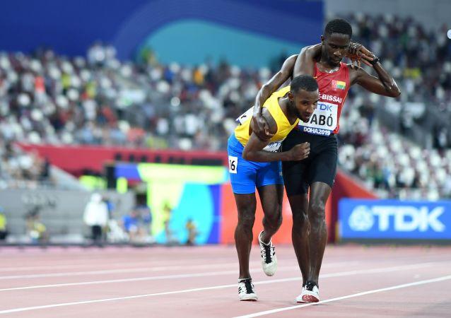 Los atletas Jonathan Busby, de Aruba, y Braima Dabó, de Guinea Bissau, durante el Campeonato Mundial de Atletismo de Doha en 2019