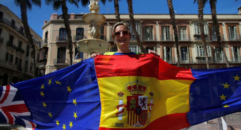 Una manifestante sostiene banderas de España, la UE y el Reino Unido durante una protesta contra el Brexit celebrada en Málaga