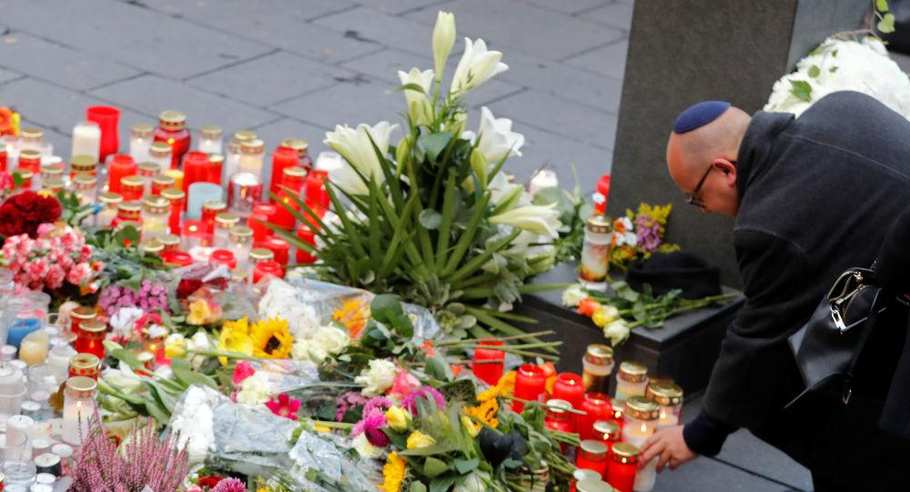 Una persona pone una vela en homenaje al tiroteo en la plaza de Halle