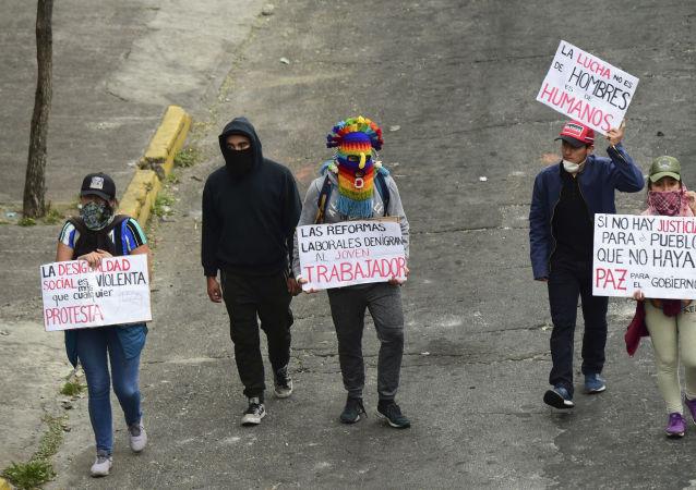 Jóvenes indígenas se manifiestan mientras el ataúd de su difunto líder, Inocencio Tucumbi, es llevado a la Casa de la Cultura en Quito, Ecuador