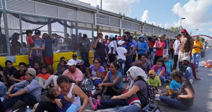 Migrantes protestando en el puente internacional que conecta a la ciudad de Matamoros, México, con Brownsville, EEUU