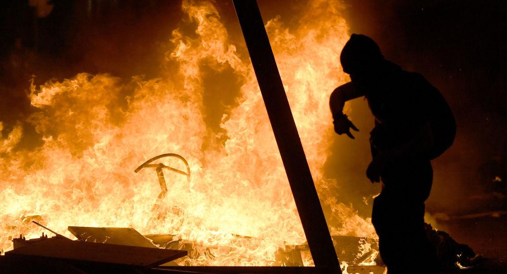 Un manifestante camina entre las barricadas en llamas durante una manifestación en Barcelona