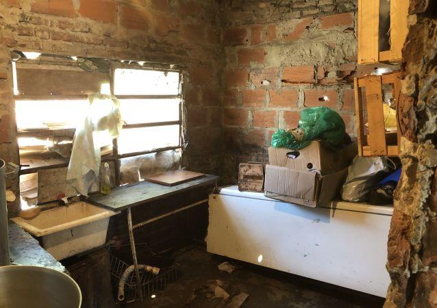 Interior de un comedor barrial, donde el agua tiró abajo la heladera