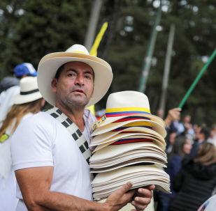 Un hombre lleva los sombreros con las banderas colombianas