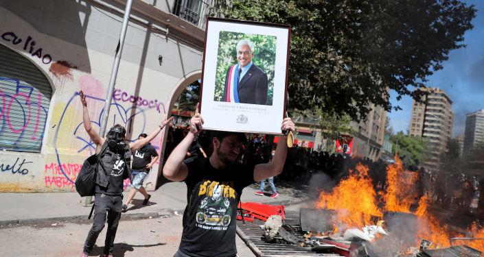 Un manifestante con la imagen del presidente chileno Sebastián Piñera