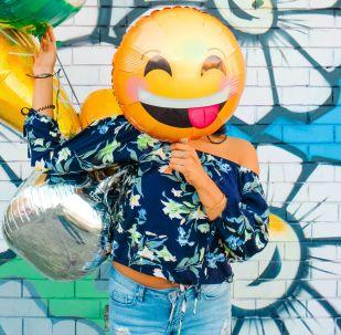 Una persona sostiene un balón de emoji sobre su rostro