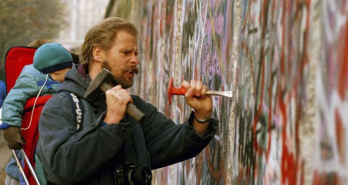 Un hombre con su bebé en la espalda usa un martillo y un cincel para tallar un pedazo del Muro de Berlín Un hombre con su bebé en la espalda usa un martillo y un cincel para tallar un pedazo del Muro de Berlín Un hombre con su bebé en la espalda usa un martillo y un cincel para tallar un pedazo del Muro de Berlín Un hombre con su bebé en la espalda usa un martillo y un cincel para tallar un pedazo del Muro de Berlín