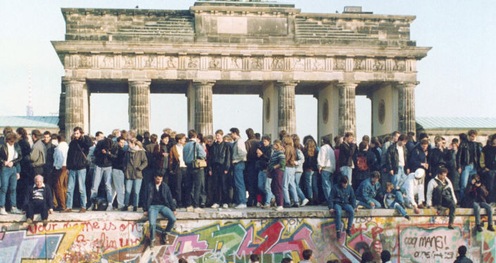 Alemanes de ambos lados se paran en el Muro de Berlín frente a la Puerta de Brandenburgo