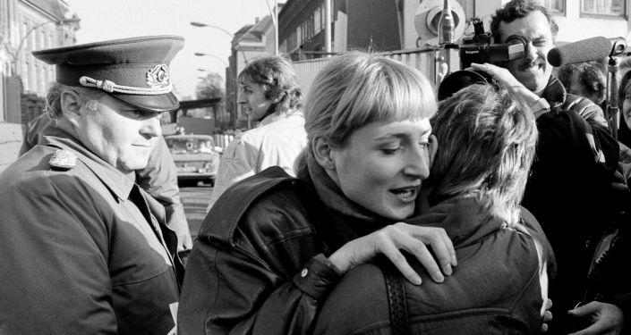 Ciudadanos de Berlín oriental y occidental se abrazan tras la caída del muro mientras un soldado fronterizo los observa