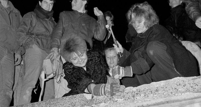 Berlineses rompen con martillo y cincel una sección del Muro de Berlín después de que se anunciara la apertura de la frontera de Alemania Oriental