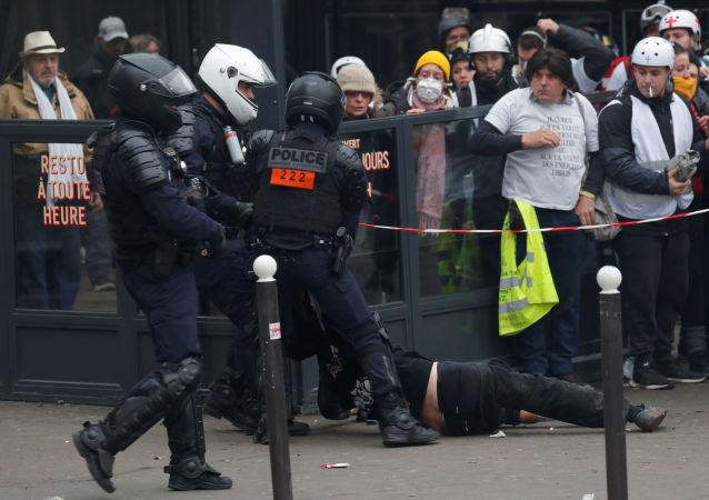 Policía arrestando a un manifestante durante las manifestaciones de los chalecos amarillos en París, Francia