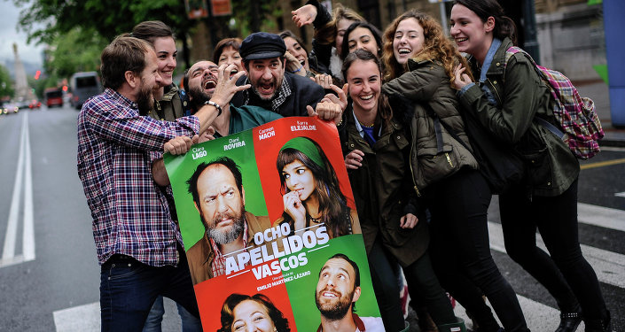 Spanish actors, Karra Elejalde, fourth left, beside his colleagues Alfonso Sanchez and Alberto Lopez, left, are surrounded by fans while they pose for a photograph holding a poster to promote their film ''Ocho Apellidos Vascos''