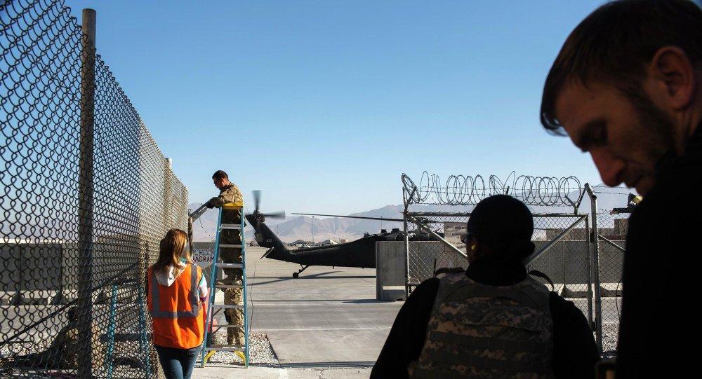Солдат ремонтирует колючую проволоку на авиабазе США Баграм в Афганистане 10 декабря 2014