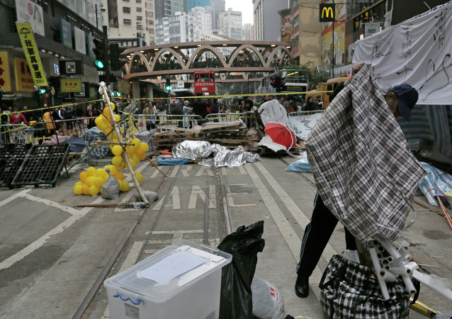 A protester packs up his belongings before police start to clear barricades and tents on a main road in the occupied areas at Causeway Bay district in Hong Kong Monday, Dec. 15, 2014