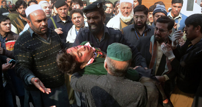Hospital security guards carry a students injured in the shootout at a school under attacked by Taliban gunmen in Peshawar, Pakistan,Tuesday, Dec. 16, 2014