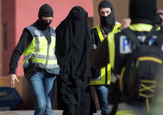 Masked Spanish police officers lead a detained woman in Melilla, December 16, 2014