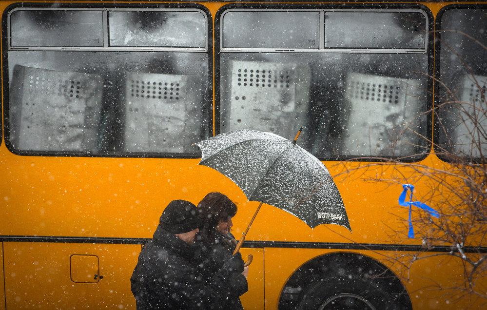 Прохожие идут мимо автобусов с сотрудниками правоохранительных органов МВД Украины у здания кабинета министров Украины в Киеве