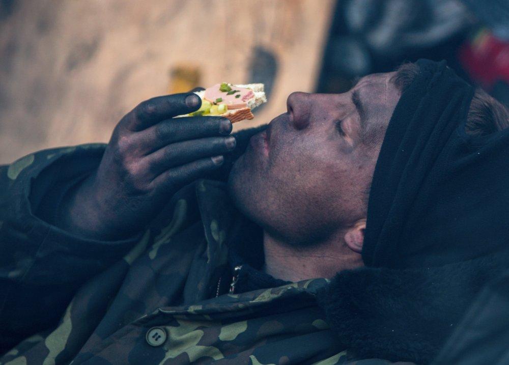Участник акции оппозиции ест бутерброд на баррикаде на улице Грушевского в Киеве