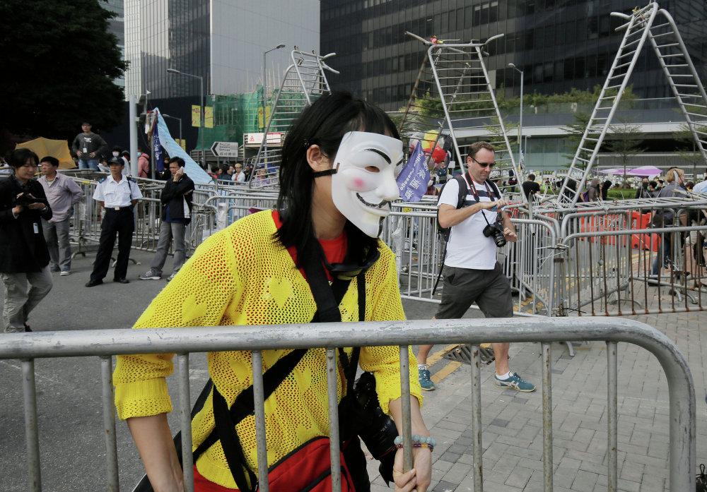 Протестующий убирает баррикады из оккупированной зоны за пределами штаб-квартиры правительства Гонконга