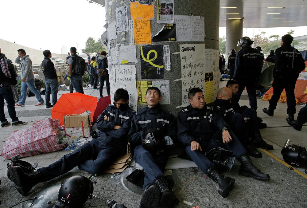 Полицейские отдыхают после столкновений у здания Законодательного совета Гонконга