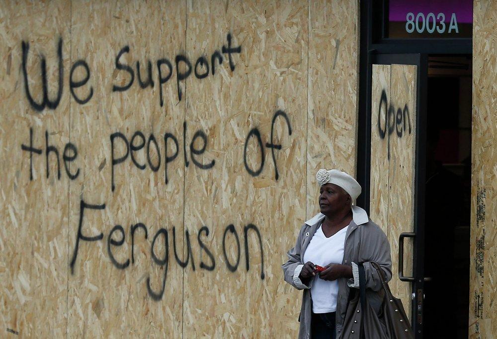 Женщина идем мимо заколоченного бизнес-центра в Фергюсоне, около которого был застрелен Майкл Браун