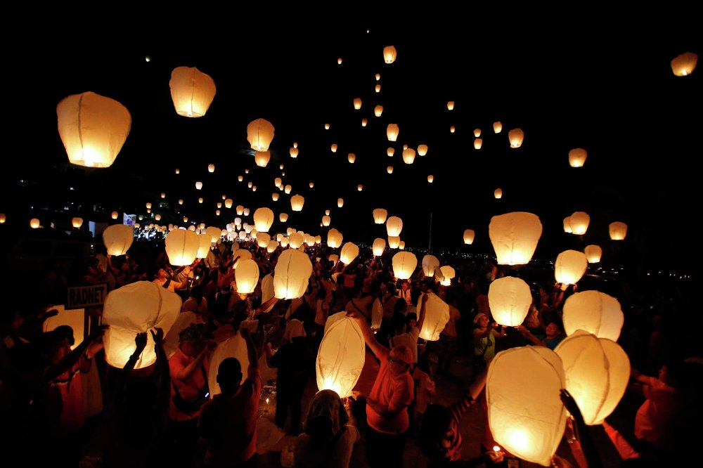 Typhoon survivors, rescuers and aid workers release sky lanterns to commemorate the victims who perished during the onslaught of Typhoon Haiyan a year ago in Tacloban city, central Philippines, November 8, 2014.